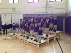 Primary school class on a tiered StackaStage portable modular stage system for schools