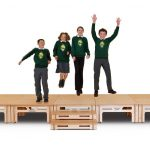 Children jumping on a StackaStage stage for schools