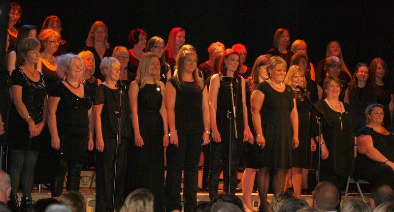 Choir singers of Harwich Sing standing on a tiered choir riser and stage kit by StackaStage